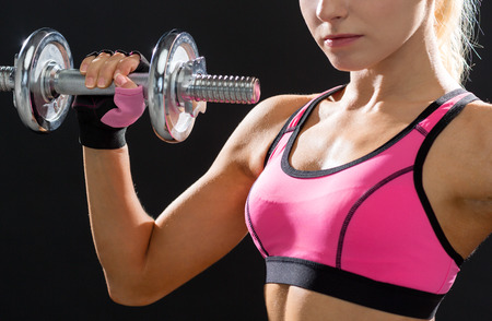 fitness, healthcare and dieting concept - close up of young sporty woman with heavy steel dumbbell Stock Photo