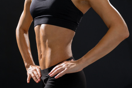 six girls: fitness and diet concept - close up of beautiful athletic female abs in sportswear
