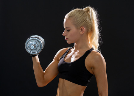 musculine: fitness, healthcare and dieting concept - young sporty woman with heavy steel dumbbell