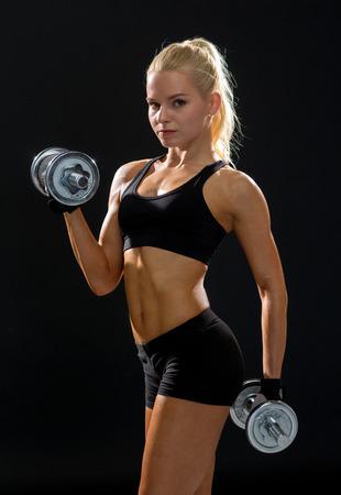 フィットネス、運動やダイエットのコンセプト - 重い鋼ダンベルを持つスポーティな女性