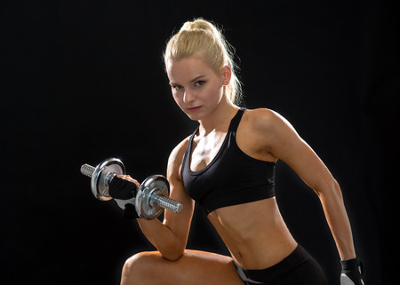 fitness, healthcare and dieting concept - young sporty woman with heavy steel dumbbell photo