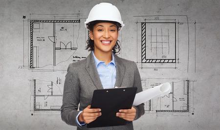 建物、開発、建設、建築コンセプト - 白いヘルメットをクリップボードと青写真の笑みを浮かべて女性実業家