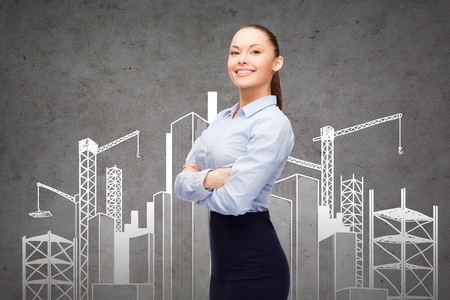 business, building and education concept - friendly young smiling businesswoman with crossed arms and construction site on the back photo
