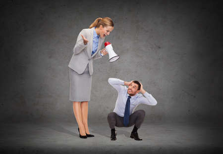 business, communication and office concept - angry businesswoman with megaphone screaming at businessman photo