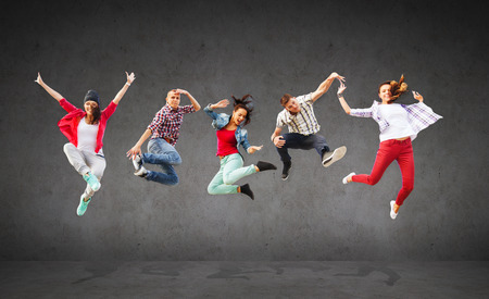 smiling teenagers: summer, sport, dancing and teenage lifestyle concept - group of teenagers jumping Stock Photo