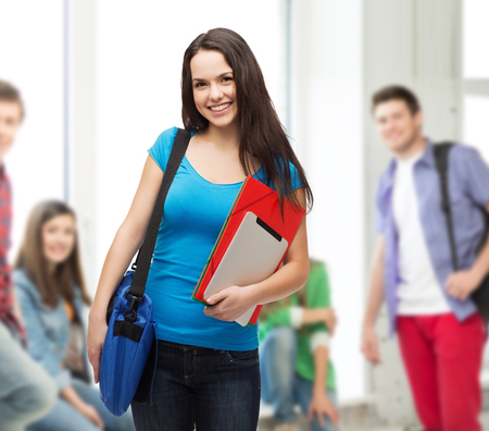 education, technology and people concept - smiling student with bag, folders and tablet pc computer standing Stock Photo