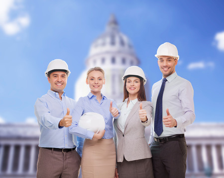 business, architecture and office concept - happy team of architects in office showing thumbs up photo