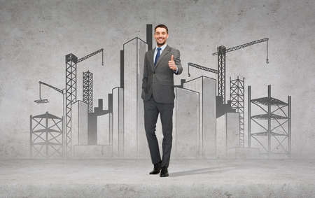 business, gesture and office concept - handsome businessman with construction site on the back showing thumbs up photo