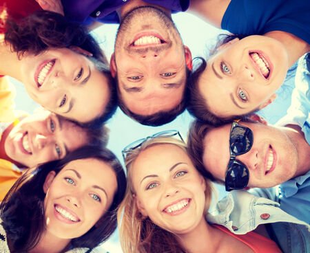 summer, holidays, vacation, happy people concept - group of teenagers looking down photo