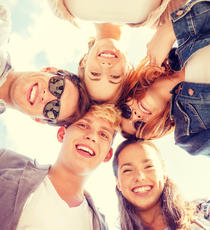 summer holidays and teenage concept - group of teenagers looking down photo