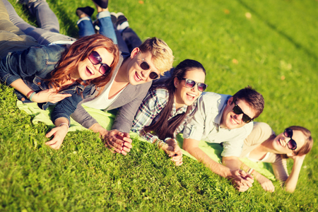 summer holidays, education and teenage lifestyle concept - group of students or teenagers lying on grass in park photo