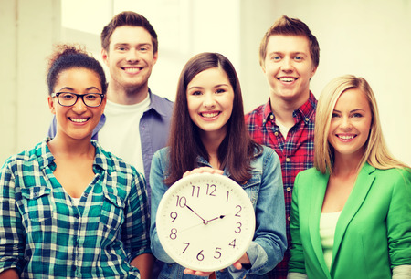education concept - group of students at school with clock photo