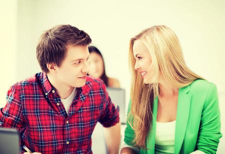 jovenes enamorados: foto de estudiantes sonrientes que miran el uno al otro en la escuela Foto de archivo