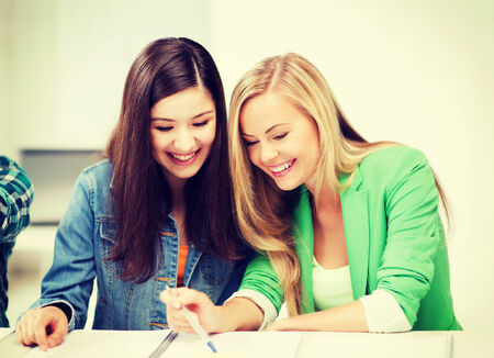 nice girl: education concept - student girls pointing at notebook at school