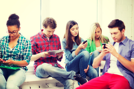 education and internet concept - students looking at their phones and tablet pc at school photo