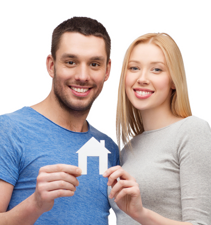 accomodation: real estate, family and couple concept - smiling couple holding white paper house