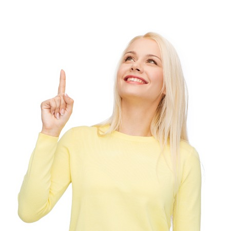 hint: advertisement concept - attractive young woman in casual clothes pointing her finger up