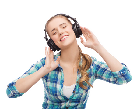 music and technology concept - smiling young woman listening to music in headphones photo