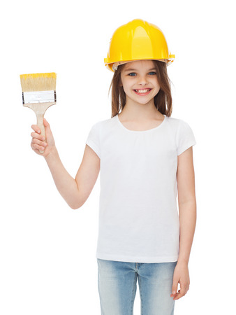 construction and people concept - smiling little girl in protective helmet with paint brush photo