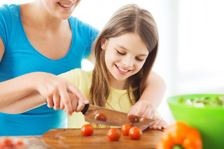 family, child, cooking and home concept - smiling little girl with mother chopping tomatoes in the kitchen photo