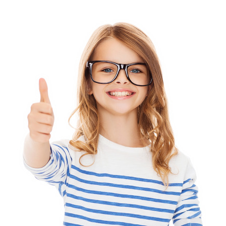 education, school and vision concept - smiling cute little girl with black eyeglasses showing thumbs up gesture photo