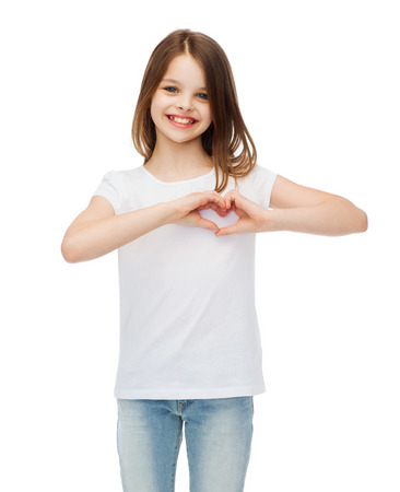 friendship, t-shirt design and happy people concept - smiling little girl in white blank t-shirts showing heart with hands photo