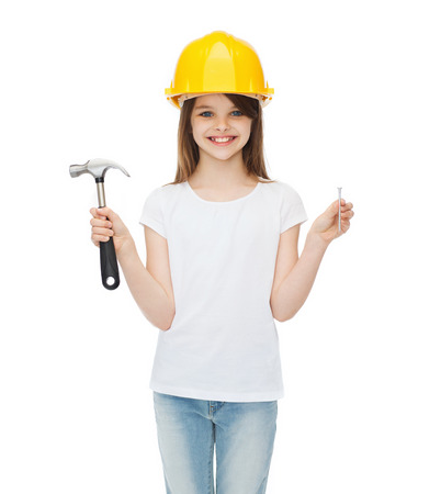 construction and people concept - smiling little girl in protective helmet with hammer and big nail