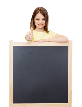 people, advertisement and education concept - happy little girl with blank blackboard showing thumbs up photo