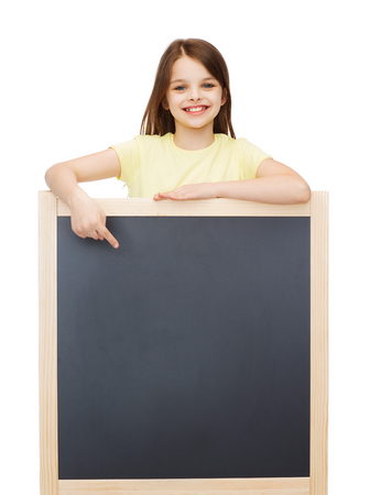people, advertisement and education concept - happy little girl pointing finger to blackboard photo