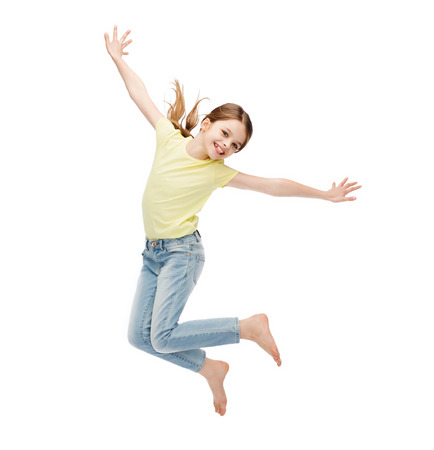 happiness, activity and child concept - smiling little girl jumping Imagens - 29245505