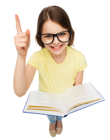 education and school concept - smiling little student girl in eyeglasses with book and finger up photo