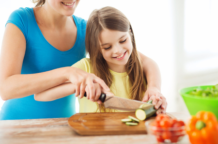 family, child, cooking and home concept - smiling little girl with mother chopping cucumber in the kitchen photo