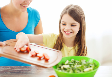 family, child, cooking and home concept - smiling little girl with mother adding tomatoes to salad in the kitchen photo