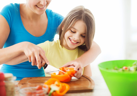 family, child, cooking and home concept - smiling little girl with mother chopping pepper in the kitchen photo