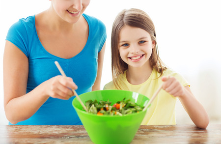 family, child, cooking and home concept - smiling little girl with mother mixing salad in the kitchen photo