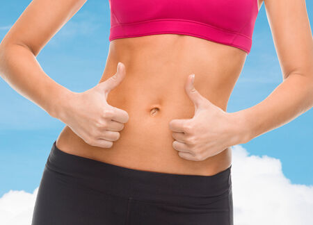thumbs up woman: fitness and diet concept - close up of female abs and hands showing thumbs up Stock Photo
