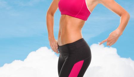 nalga: la aptitud y el concepto de dieta - de cerca de la mujer deportiva que señala en sus nalgas