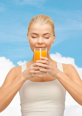 food, healthcare and diet concept - young woman drinking orange juice photo
