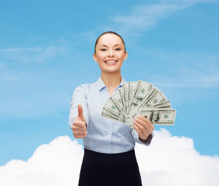 business and money concept - young businesswoman with dollar cash money showing thumbs up photo