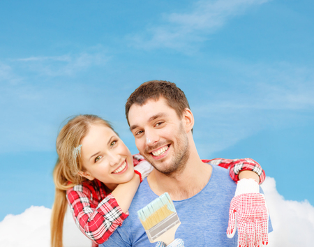 repair, building and home concept - smiling couple covered with paint with paint brush photo