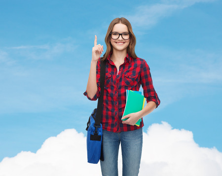 education and people concept - smiling female student in eyeglasses with bag and notebooks showing finger up over blue sky background photo