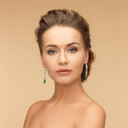 beauty and jewelry concept - beautiful woman in diamond and emerald earrings photo