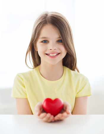 love, home, happiness and people concept - smiling little girl with red heart at home photo