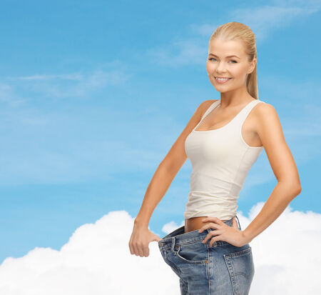 fitness, diet and healthcare concept - sporty woman showing big pants photo