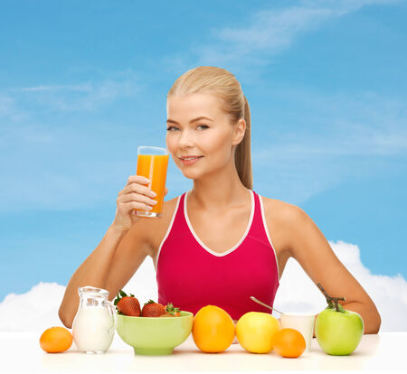 fitness, diet and healthcare concept - smiling young woman with healthy breakfast and drinking orange juice photo