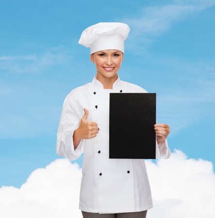 cooking, advertisement and food concept - smiling female chef, cook or baker with blank black paper showing thumbs up photo