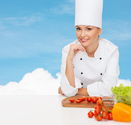 cooking and food concept - smiling female chef with vegetables photo