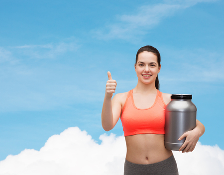 fitness and diet concept - smiling teenage girl with jar of protein showing thumbs up photo