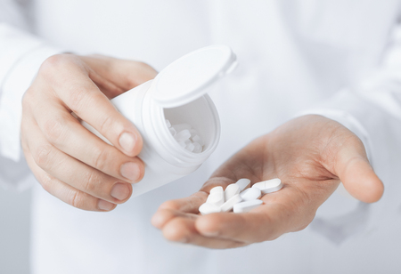 packs of pills: picture of doctor hands holding white pack and pills