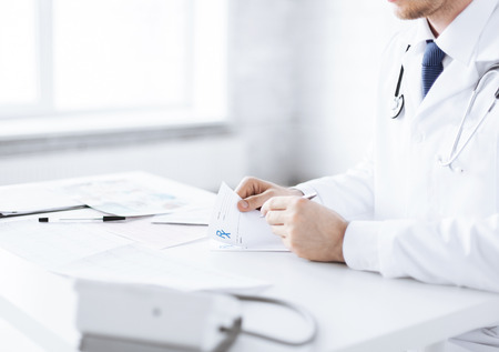 close up of male doctor writing prescription paper photo